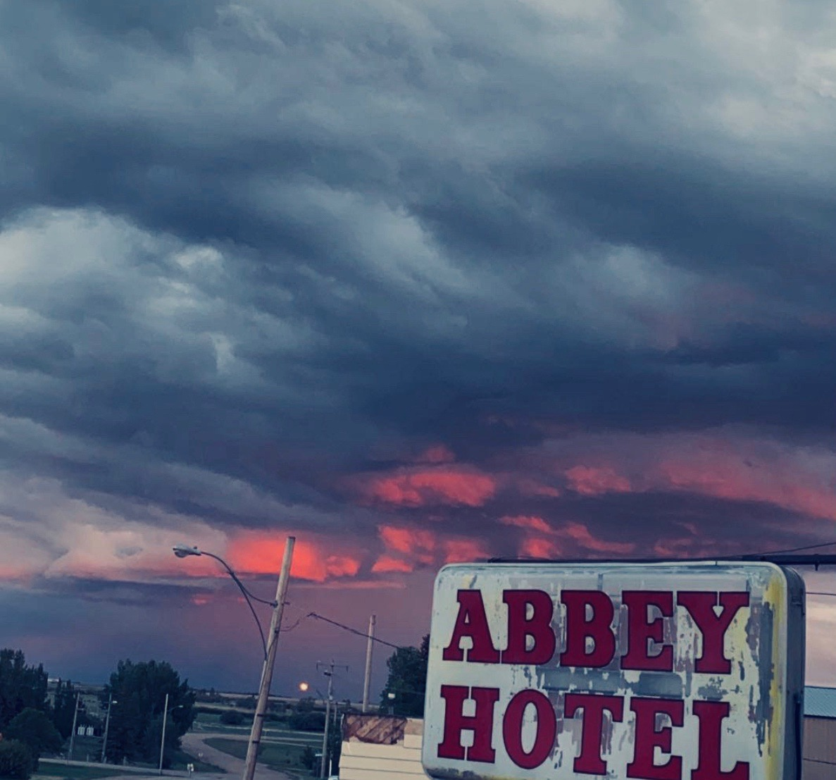 Sign of the Abbey Hotel in Swift Current highlighted against a dark and colourful night sky.